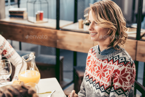 beautiful young woman in sweater at christmas table - Stock Photo - Images