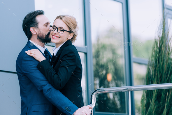 happy mature business people hugging and kissing while standing outside - Stock Photo - Images