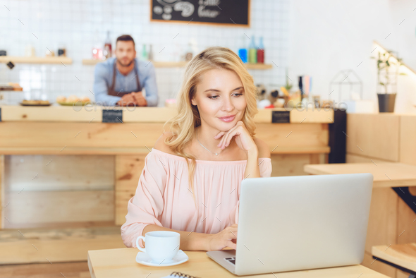 beautiful smiling young woman using laptop in cafe - Stock Photo - Images