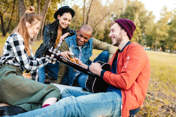 group of happy multicultural friends resting in park together - Stock Photo - Images