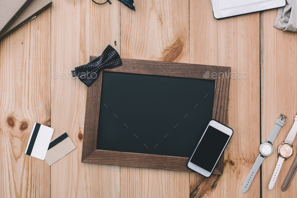 top view of smartphone with blank screen, empty photo frame with bow tie, credit cards and - Stock Photo - Images