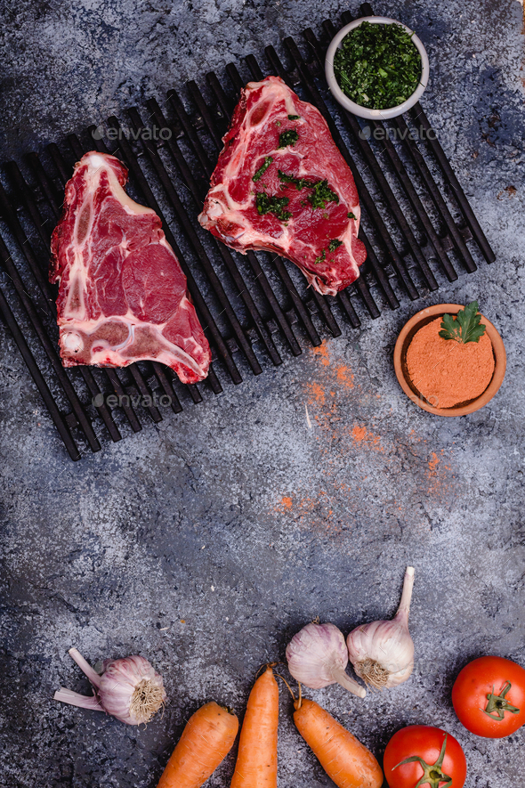 top view of raw meat with spices and vegetables on concrete table - Stock Photo - Images