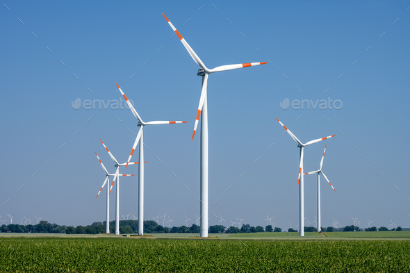 Modern wind turbines in front of a clear blue sky - Stock Photo - Images