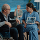 Woman nurse with x ray on tablet showing scan to old patient - PhotoDune Item for Sale