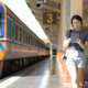 A teenage woman with headphones listening to music from an app on tablet while waiting for a train.. - PhotoDune Item for Sale