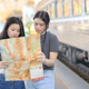Two teenage girls looking at a map to travel by train. - PhotoDune Item for Sale