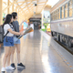 Two teenage girls looking at maps to travel by train. - PhotoDune Item for Sale