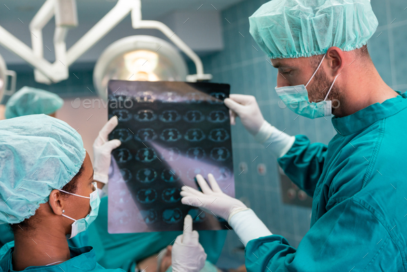 Healthcare and medical concept. Group of doctors looking at x-ray before operation - Stock Photo - Images