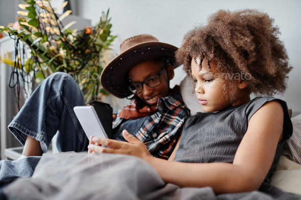 African American Kids Using Smartphone on Bed - Stock Photo - Images