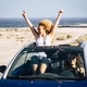 Two young women traveling in a convertible car and having fun during journey. Young woman - PhotoDune Item for Sale