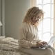 Young woman working on laptop while sitting on bed in bedroom. Businesswoman morning - PhotoDune Item for Sale