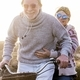 Happy senior retired couple in warm clothing enjoying a bicycle ride on field. Old couple have fun - PhotoDune Item for Sale