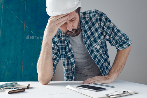 Worried construction engineer project manager after reviewing notes - Stock Photo - Images