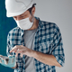 Construction engineer with protective face mask text messaging on mobile phone - PhotoDune Item for Sale