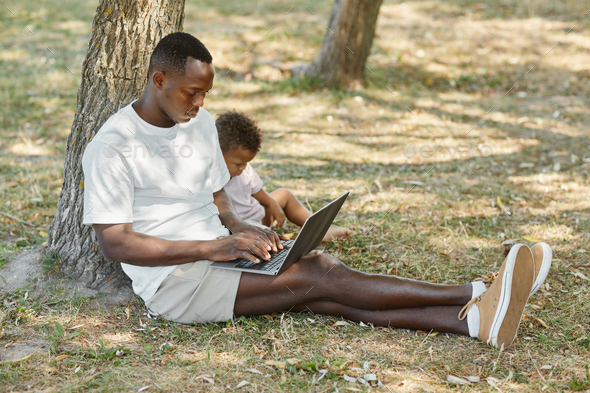 African American Father Working in Park with Son - Stock Photo - Images