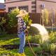 Happy woman gardener in work clothes watering the beds in her vegetable garden on sunny warm summer - PhotoDune Item for Sale