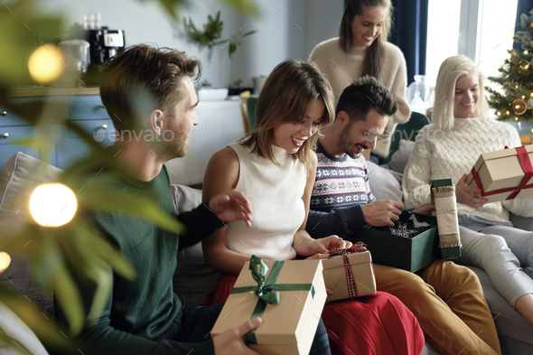 Group of friends opening Christmas presents - Stock Photo - Images