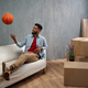 Man with basketball celebrating moving home surrounded by packing boxes, new living concept. - PhotoDune Item for Sale