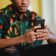 Unrecognizable young man using smartphone, sitting on sofa at home, social networks concept. - PhotoDune Item for Sale