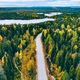 Aerial view of rural road in yellow and orange autumn forest with blue lake in Finland - PhotoDune Item for Sale
