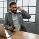 Young african american businessman with smartphone and headset working on a laptop indoors in office - PhotoDune Item for Sale