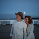 Couple in love on walk holding hands outdoors on pier by sea at moonlight, looking at view. - PhotoDune Item for Sale