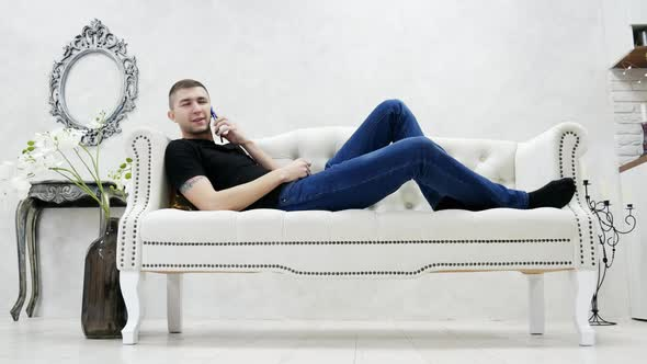 Young Man Relaxing On Couch And Speaks By Mobile Phone In Modern Luxury House Stock Footage