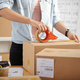 Woman Taping Parcel Box At Office - PhotoDune Item for Sale