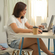 A woman working from home with a laptop in the bedroom. - PhotoDune Item for Sale