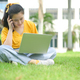 Young woman sitting on the lawn talking on the phone and using laptop. - PhotoDune Item for Sale