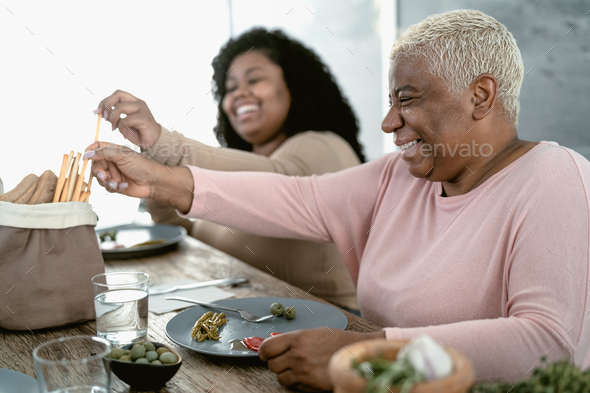 Happy Hispanic mother and daughter having healthy lunch at home - Stock Photo - Images