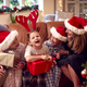 Family Wearing Santa Hats Sitting On Sofa At Home Opening Christmas Gifts - PhotoDune Item for Sale