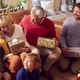 Multi-Generation Family Exchanging And Opening Gifts Around Christmas Tree At Home - PhotoDune Item for Sale
