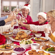 Multi Generation Family In Santa Hats Making Toast Whilst Eating Christmas Meal At Home Together - PhotoDune Item for Sale