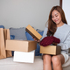 A woman receiving and opening a postal parcel box of clothing at home for delivery - PhotoDune Item for Sale