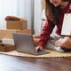 A woman using laptop for online shopping , holding shopping bags and opening postal parcel box - PhotoDune Item for Sale
