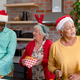 Three diverse senior male and female friends in christmas hats cooking together in kitchen - PhotoDune Item for Sale