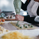 Woman preparing fresh made ravioli with ricotta cheese and spinach inside pasta factory - PhotoDune Item for Sale