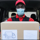 African delivery man carrying cardboard box while wearing face mask to avoid corona virus spread - PhotoDune Item for Sale