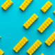 Yellow Plastic Building Blocks On Turquoise Blue Background With Copy Space - PhotoDune Item for Sale