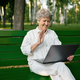 Drandma using laptop on the bench in summer park - PhotoDune Item for Sale