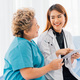 Overjoyed Asian female cardiologist using digital tablet while working with elderly female patient - PhotoDune Item for Sale
