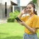 Asian teenage girl wearing music headphones looking at camera happy faces. - PhotoDune Item for Sale