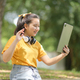 Asian teen girl greets her friends with a tablet. - PhotoDune Item for Sale