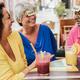 Multiracial senior women having fun playing guessing forehead game at bar restaurant - PhotoDune Item for Sale