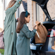 Cute girl putting her backpack in car trunk while her mom opening it - PhotoDune Item for Sale