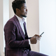 African businessman in suit scrolling in smartphone in front of camera - PhotoDune Item for Sale