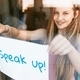 Speak up! paper, young girl showing sign through glass window - PhotoDune Item for Sale