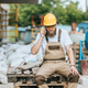 builder in hardhat and protective googles smoking cigarette and talking on smartphone at - PhotoDune Item for Sale