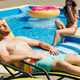 handsome young man tanning on sun lounger while his girlfriend sitting on poolside - PhotoDune Item for Sale